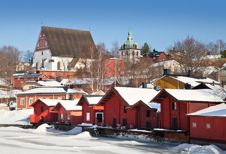 vibrant cottage: Red wooden houses on the river coast in Porvoo town, Finland  winter season  Stock Photo