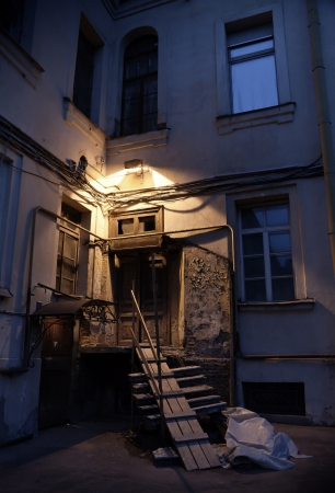 abandoned house: Old door with lamp and wooden stairs at night