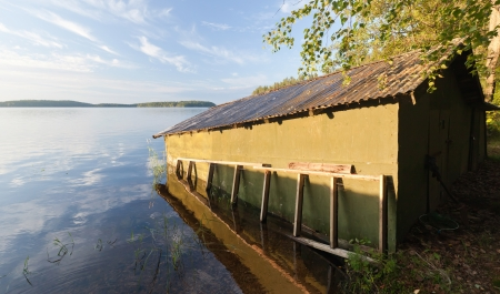 Small green wooden boat garage on the coast of Saimaa lake, typically construction for Finland photo