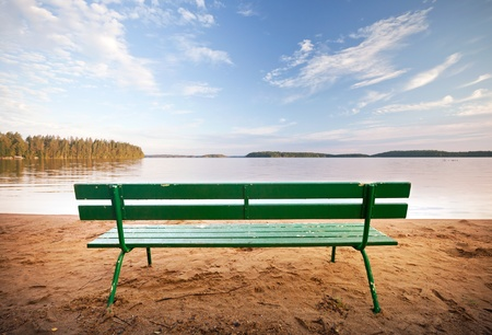 settle back: Green wooden bench in front of the lake coast