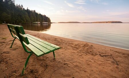 settle back: Green wooden bench on the coast of the lake in the morning light