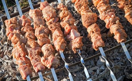 Shish kebab. Slices of meat with sauce cooking on hot coals photo