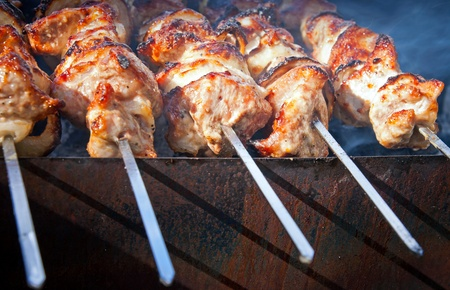 Shish kebab  slices of meat with sauce preparing on fire photo
