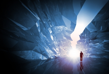 the end: Man walks through the fantasy crystal corridor with rugged walls and bright glowing end Stock Photo