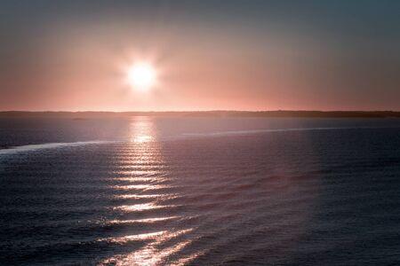sol naciente: Temprano en la mañana en el lago Paisaje con Sol naciente y las ondas que cruzan