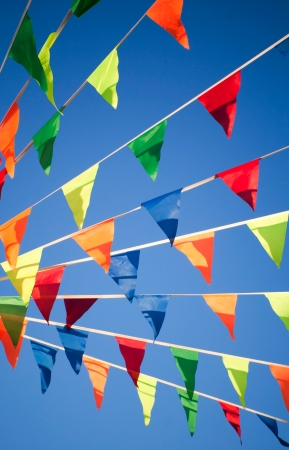 Bright colorful triangle flag banner above blue sky background Stock Photo