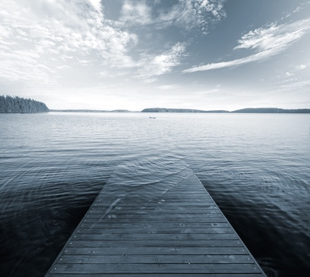 Old wooden pier goes under deep blue water  Monochrome photo Stock Photo
