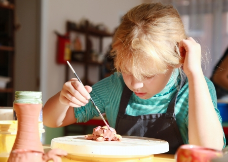 Little girl is painting handmade clay sculpture in the pottery workshop