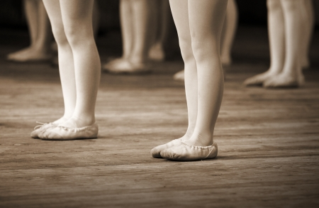 ballet shoes: The ballet school fragment with little girls legs on pointes