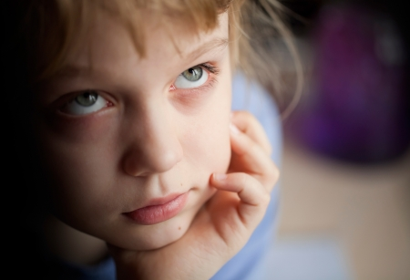 misses: Little girl is boring and misses for something  Closeup portrait with shallow depth of field