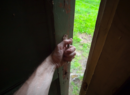 Hand of a man opening old door from the dark room into the fresh green scene  Back to the nature metaphor photo