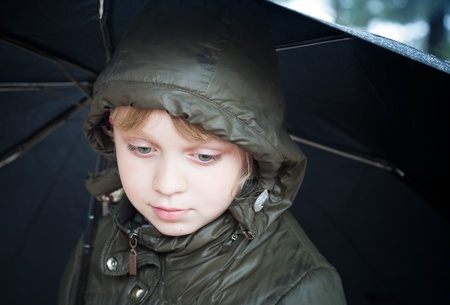 Portrait of a little blond girl with umbrella in a casual jacket with the hood photo