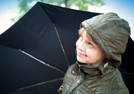 Portrait of a smiling little blond girl with umbrella in a casual jacket with the hood photo