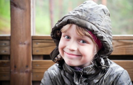 Portrait of a smiling little blond girl  in a casual jacket with the hood photo