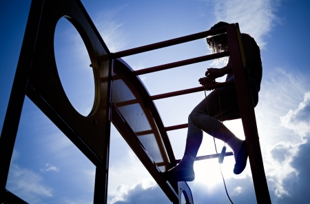 Silhouette of a little girl  on a outdoor playground equipment above blue sky background photo