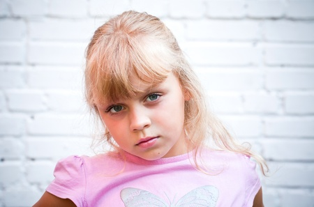 fair haired: Portrait of a little blond beautiful Russian girl above white brick wall background