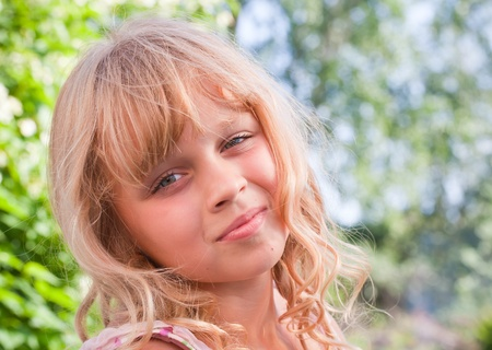 blond brown: Portrait of a slightly smiling little blond beautiful Russian girl above nature outdoor background