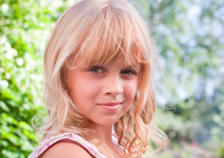 Portrait of a slightly smiling little blond beautiful Russian girl above nature outdoor background photo