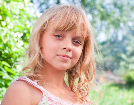 belle: Portrait of a slightly smiling little blond beautiful Russian girl above nature outdoor background