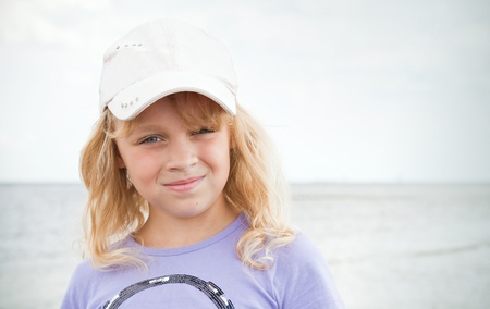 blond brown: Portrait of a slightly smiling little blond beautiful Russian girl on the sea coast