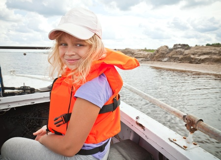 Little girl on a small boat wears bright orange life-jacket photo