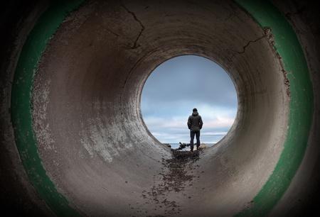 Man kijkt naar horizon aan het einde van donkere betonnen tunnel Stockfoto