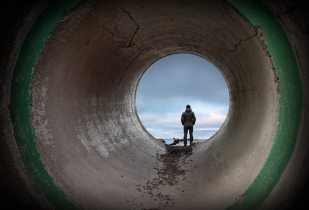 Man looks at horizon in the end of dark concrete tunnel photo