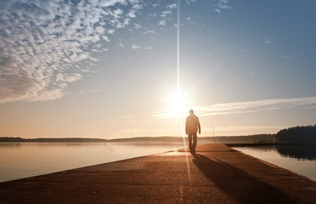 dream lake: A man goes on the concrete pier in the sunrise Stock Photo