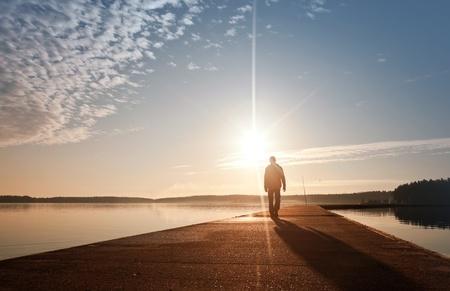 hombre solitario: Un hombre va en el muelle de concreto en la salida del sol