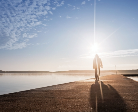 A man goes on the concrete pier in the sunrise Stock Photo - 15658808
