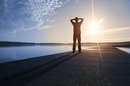 A man stands on the concrete pier starring at the Sun