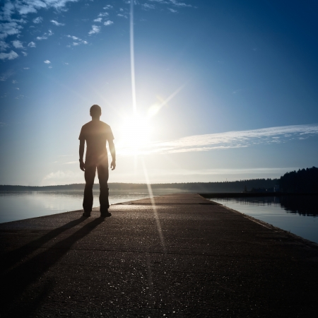 docks: A man stands on the concrete pier starring at the setting Sun