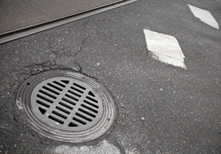 manhole: Sewer manhole cover on the roadside Stock Photo