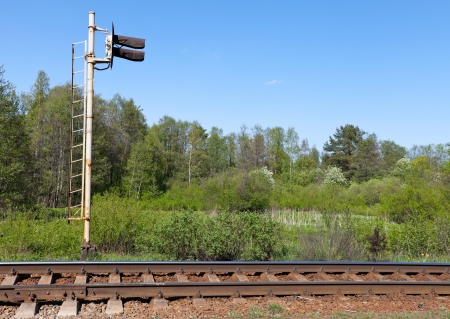 Railway fragment with semaphore and forest on a background photo