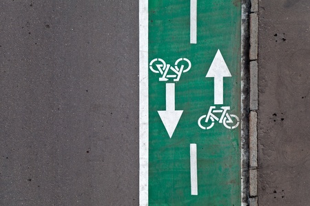 and opposite: Green bicycle lane with road marking background texture