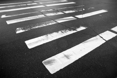 Danger pedestrian crossing with white rectangles and emergency braking tracks on the dark wet asphalt road Stock Photo