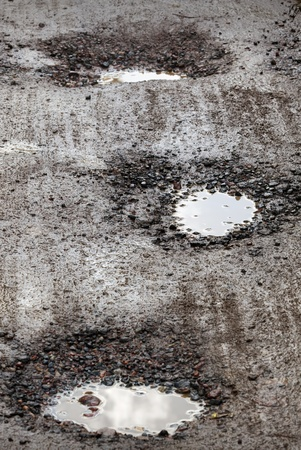 Damaged wet road with holes photo