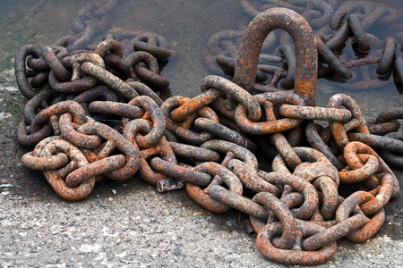 Rusty ship chain on the stone coast photo