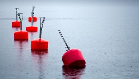 buoys: Yachts moorings buoys of small European marina under the rain Stock Photo