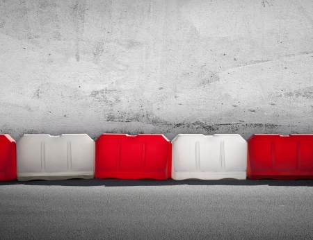 under control: Red and white road barrier above concrete wall Stock Photo