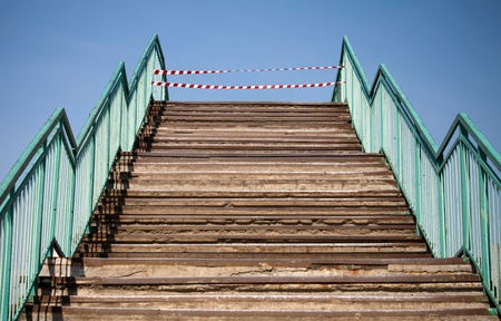 margin of safety: Abstract concrete structure with footsteps and prohibiting red and white striped tapes at the end Stock Photo