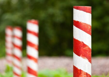 margin of safety: Red and white striped poles in the row