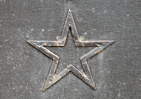 Close-up photo of a rusted five-point star on the metal wall photo