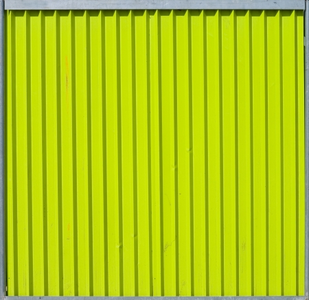 Texture of bright green-yellow ridged metal fence section photo