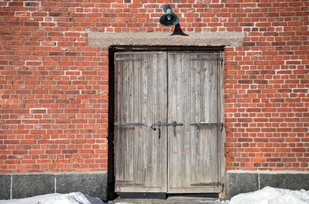 Brick wall of an old building with old weathered wooden gate Stock Photo - 15841088