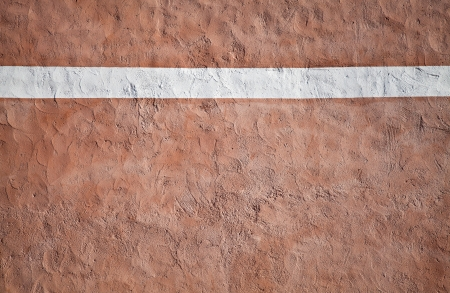 Closeup red painted stone wall texture with red plaster and white stripe photo