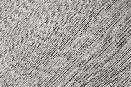 Closeup rough gray concrete wall texture with relief lines photo
