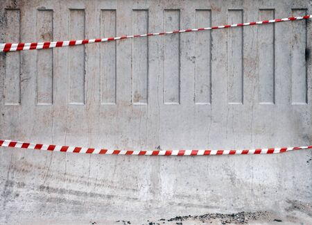 margin of safety: Texture of red and white striped tapes on concrete barrier
