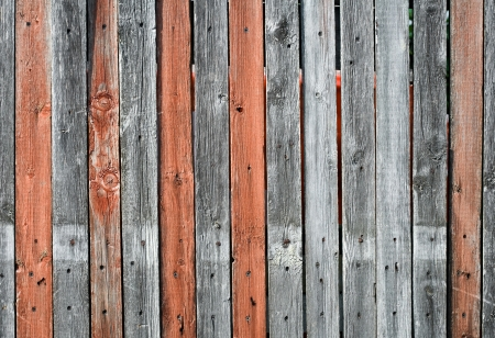Close-up view of an old wooden fence with gray and orange mixed planking photo