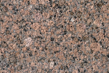 Close-up relief texture of red granite stone photo